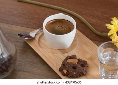 Gourmet hot Americano coffee brewed in a small cup . With shock chocolate cookies delicious . Suitable for breakfast every day.