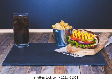 Gourmet hot dog with chips and drink on dark background. Tabletop, front view.