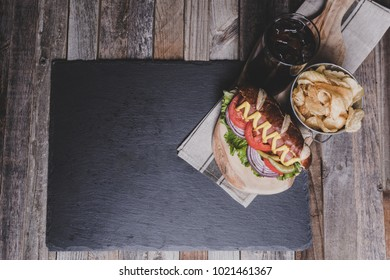 Gourmet hot dog with chips and drink on dark background. Tabletop, top view.