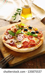 Gourmet Italian four seasons pizza with all the toppings including prosciutto ham, olives, mushrooms, cheese, tomato, onion, rocket and basil for a delicious savoury meal