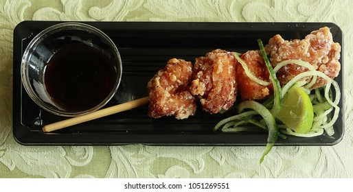 Gourmet Japanese karrage fried chicken with lemon sauce on black tray