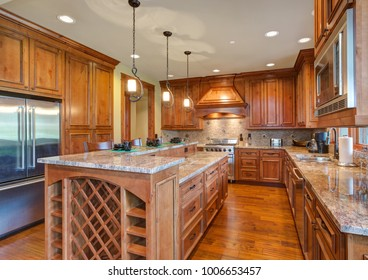 Gourmet kitchen boasts a bar style kitchen island with built-in wine rack, maple cabinets with granite countertops and mosaic backsplash. Northwest, USA