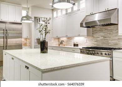 La cocina gourmet está equipada con vajilla blanca con encimeras de mármol, fregadero de baldosas en el metro de piedra, nevera de acero inoxidable de doble puerta y magnífica isla de cocina. Noroeste, Estados Unidos