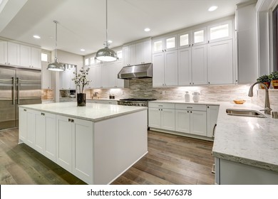 Gourmet kitchen features white shaker cabinets with marble countertops, stone subway tile backsplash, double door stainless steel refrigerator and gorgeous kitchen island. Northwest, USA