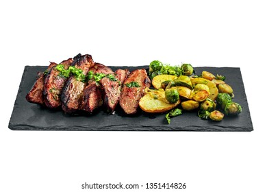 Gourmet meal made of hanger steak, brussels sprouts, potatoes and onion on a stone board. Tasty medium rare meat steak with vegetables isolated on a white background.