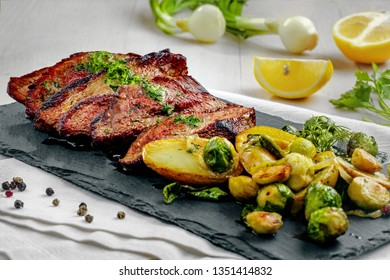 Gourmet meal made of hanger steak, brussels sprouts, potatoes and onion on a stone board. Tasty medium rare meat steak with vegetables on a white wooden table.
