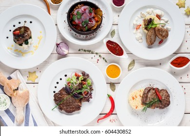 Gourmet meat meals assortment flat lay. Top view on restaurant table with menu of tasty grilled snacks. Buffet, appetizing, delicious food, barbecue concept