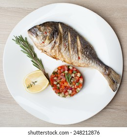 Gourmet Mediterranean seafood dish. Grilled fish gilthead served with vegetable salsa, lemon, rosemary on white plate top view