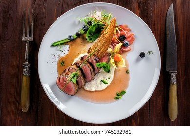 Gourmet medium rare meat steak with sauce and fresh salad. Healthy meal made of meat fillet and fresh vegetables on a rustic table. Top view.