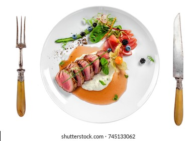 Gourmet medium rare meat steak with sauce and fresh salad. Healthy meal made of meat fillet and fresh vegetables isolated on white background. Top view.