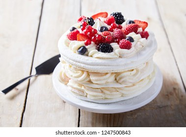 Gourmet pavlova cake with fresh berry topping and layers of whipped cream and meringue served on a plate with a spatula in a close up view