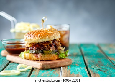 Gourmet Pulled Pork Burger with with Coleslaw and barbecue Sauce on  Wooden Table.
