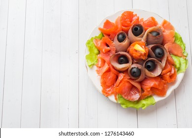 Gourmet restaurant serving a plate of smoked salt, raw white fish fillets and salmon. Delicacy fresh seafood dish with catfish, salmon meat with olives on a plate Copy space.