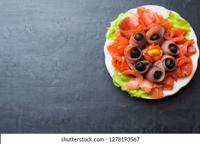 Gourmet restaurant serving a plate of smoked salt, raw white fish fillets and salmon. Delicacy fresh seafood dish with catfish, salmon meat with olives on a plate close-up.