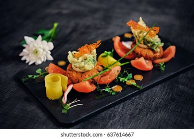 Gourmet seafood snacks with tomatoes on a wooden table surface.