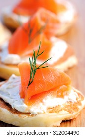 Gourmet smoked salmon and cream cheese blinis on a wooden platter