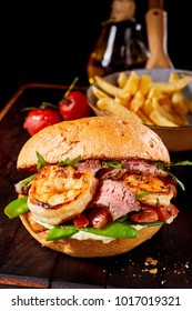 Gourmet Surf and Turf seafood and meat burger with medium rare roast beef, scampi, mangetout peas, rocket and tomato served with potato chips