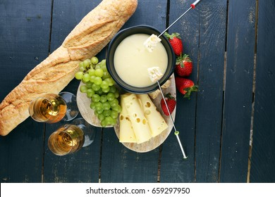 Gourmet Swiss fondue dinner with assorted cheeses on a board alongside a heated pot of cheese fondue with two forks dipping bread and white wine behind in a tavern or restaurant