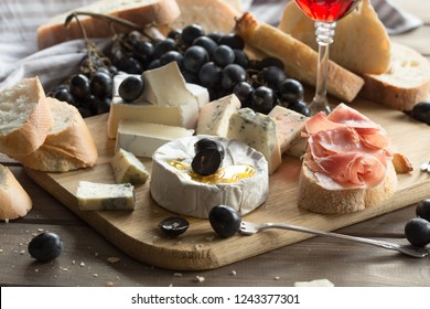 Gourmet Swiss fondue dinner on a winter evening with assorted cheeses on a board  and red wine behind in a tavern or restaurant