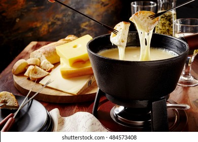 Gourmet Swiss fondue dinner on a winter evening with assorted cheeses on a board alongside a heated pot of cheese fondue with two forks dipping bread and white wine behind in a tavern or restaurant
