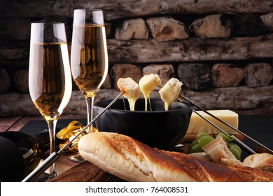 Gourmet Swiss fondue dinner on a winter evening with assorted cheeses on a board alongside a heated pot of cheese fondue with two forks dipping bread and white wine or champagne