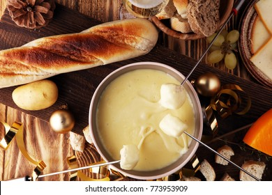 Gourmet Swiss fondue dinner on a winter evening with assorted cheeses on a board alongside a heated pot of cheese fondue with two forks dipping bread and white wine behind in a tavern or restaurant.
