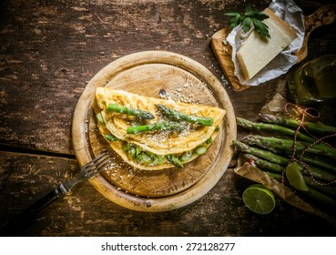 Gourmet Tasty Egg Omelette with Asparagus and Cheese on Top of Wooden Round Cutting Board, Served on Rustic Wooden Table, Captured in High Angle View.