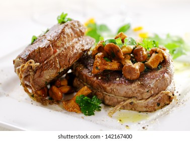 Gourmet thick juicy fillet steak medallions grilled to perfection and served topped with fried wild mushrooms and herbs