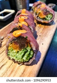 Gourmet tuna and cucumber sushi roll on wooden plank