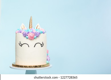 Gourmet unicorn cake with pink and purple buttercream frosting on blue background.