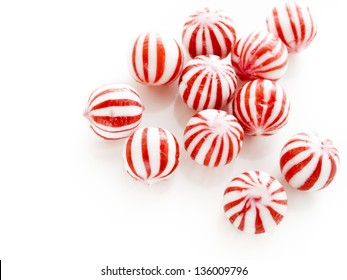 Gourmet white and red peppermint candies on white background.