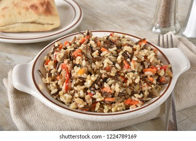 Gourmet wild rice pilaf with carrots, peppers, and sauce with a dinner roll.