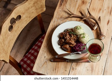 Gourmet wild venison goulash with dumplings seasoned with fresh herbs and served with red cabbage and glass of wine on a rustic table decorated with deer antlers in a high angle view