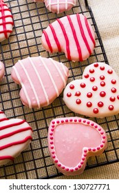 Gourtmet heart shaped cookies decorated for Valentine's Day on drying rack.