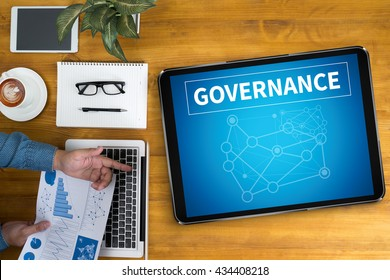 GOVERNANCE Businessman working at office desk and using computer and objects, coffee, top view,