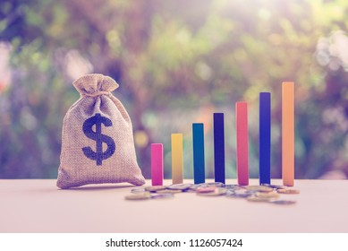 Government budget / public spending concept : Dollar bag, coins, color wood bar graph on a table, depicts the increment in annual financial budget or revenues that government collects from tax payer.