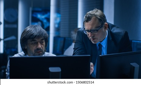 Government Chief of Cyber Security Consults Operations Officer who Works on Computer. Specialists Working on Computers in System Control Room.