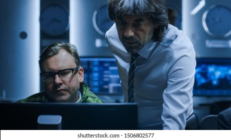 Government Chief of Cyber Security Consults Military Officer who Works on Computer. Specialists Working on Computers in System Control Room.