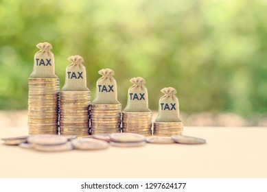 Government income tax collection concept : Tax burlap bags on rows of rising coins, depicts the levying of taxes that aims to raise revenue to fund governing or alter prices in order to affect demand