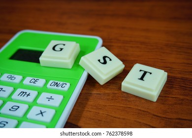 Government Services Tax or Good Services Tax or shortform as GST with green calculator on wooden background. Selective focused.