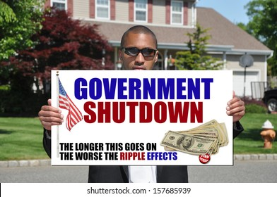 Government Shutdown Stop Payment Ripple Effects Sign in hand of African American Businessman in Suburban Neighborhood USA