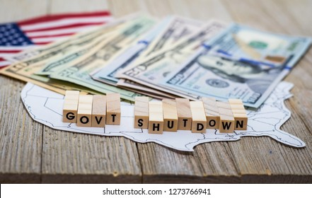 Government Shutdown USA concept with American flag and dollar bills on white background and wooden board