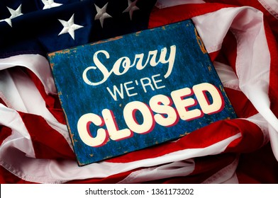 Government shutdown, Washington is broken, political deadlock and partisan politics concept theme with a sorry we're closed sign and the American flag
