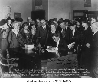 Governor Emmett D. Boyle of Nevada signing resolution for ratification of Nineteenth Amendment to Constitution of U.S. as a group of suffragists watch.