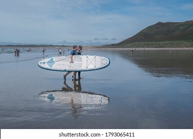 Gower Peninsula, UK - 7 August 2020:  Two women surfers carry their surfboard back onto the beach of Rhossili Bay, on the Gower Peninsula near Swansea, Wales.