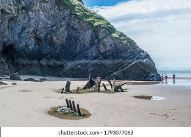 Gower Peninsula, UK - 7 August 2020:  Scenic view of people exploring the ship wrecks, pools and cliffs of Rhossili Bay beach, on the Gower Peninsula near Swansea, Wales.
