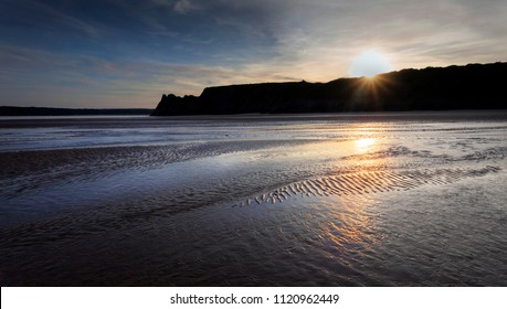 Gower sunset and wet sand at The Great Tor and Three Cliffs Bay, Swansea, Wales, UK