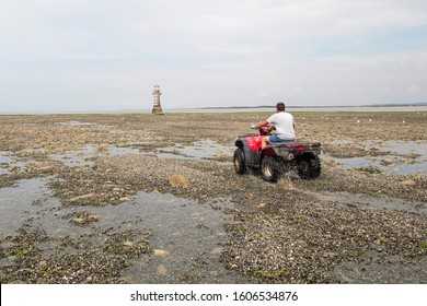Gower, UK: July 11, 2018: A cockle picker is driving away from the camera on a quad bike. The cockle industry is a thriving business off the north Gower coast.