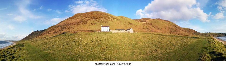 Gower, UK: May 03, 2019: White farmhouse in a remote, rural location with outbuildings and a sea view.