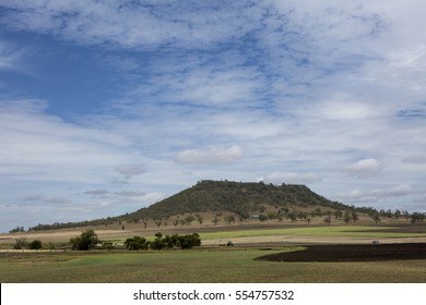 Gowrie Mountain, Toowoomba, Queensland Australia: Flat topped Gowrie Mountain with rural lands in the foreground and a white cloudscape above. Toowoomba lies in the crater of a very old volcano.